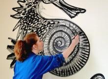 Maria Dubin painting a seahorse, symbol of international friendship