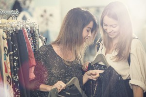 Young friends searching clothes in secondhand clothing shop